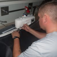 A Boatswain in works to sew some privacy curtains.