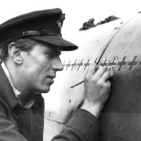 "With meticulous care, Beurling chalks up his ""kills"" on the fuselage of his Spitfire."
