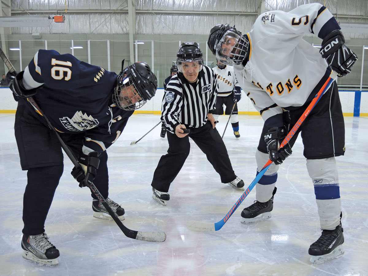 On the left, PO1 Marc Buzzi of Team Howlett and CPO2 Josh Barnes get set for the opening puck drop by referee CPO2 Yves Ouellet. Photo by Peter Mallett, Lookout