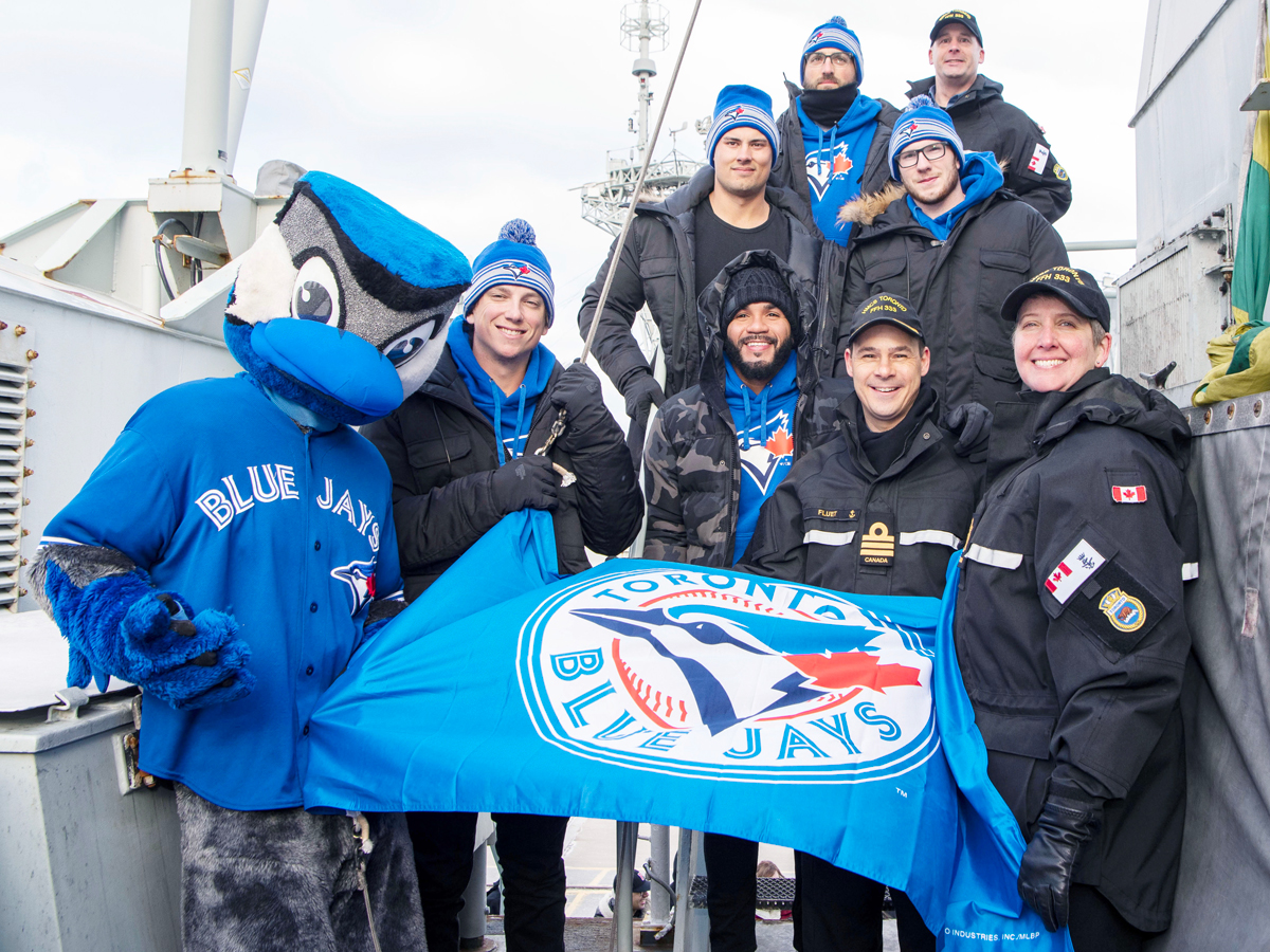 The Blue Jays, their mascot Ace, and HMCS Toronto's command team display the Blue Jays' pennant. From left: Ace, Toronto Blue Jays Mascot; Ryan Borucki (player); Devon Travis (player); Cdr Martin Fluet, Commanding Officer, HMCS Toronto; and CPO1 Alena Mondelli, Coxswain, HMCS Toronto. Second row, Luke Maile (player); and Dan Jansen (player). Back row: Kevin Pillar (player) and LCdr Matthew Woodburn, Executive Officer, HMCS Toronto. Photo by Mona Ghiz, MARLANT PA