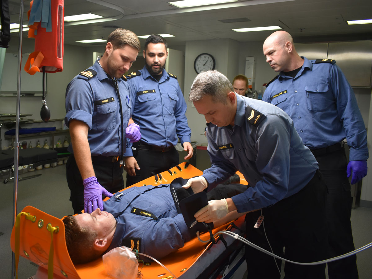 Earlier in the year, Lt(N) Drake (left, foreground) led a casualty treatment exercise onboard MV Asterix. LS Stowell (right, foreground) applies a blood pressure cuff while MS Peer (left) and MS Robillard (right) look on.