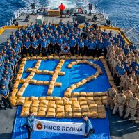 HMCS Regina's crew poses with over 3,000 kilograms of narcotics seized from a dhow on April 15 during Operation Artemis in the Pacific Ocean. Photo by Corporal Stuart Evans, Borden Imaging Services