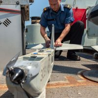 An unmanned aerial vehicle (UAV) controller assembles the UAV onboard HMCS Whitehorse during Operation Caribbe. Photos by Operation Caribbe Imagery Technician