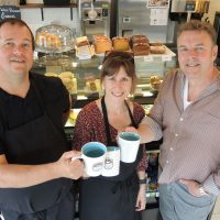 From left: Kindness Ambassador Greg Hind is joined by A Kinder Cup owners Chief Petty Officer First Class (Retired) Marc Dufort and Kim Dufort as they raise a toast to their new coffee shop at Admirals Walk Plaza. Photo by Peter Mallett, Lookout