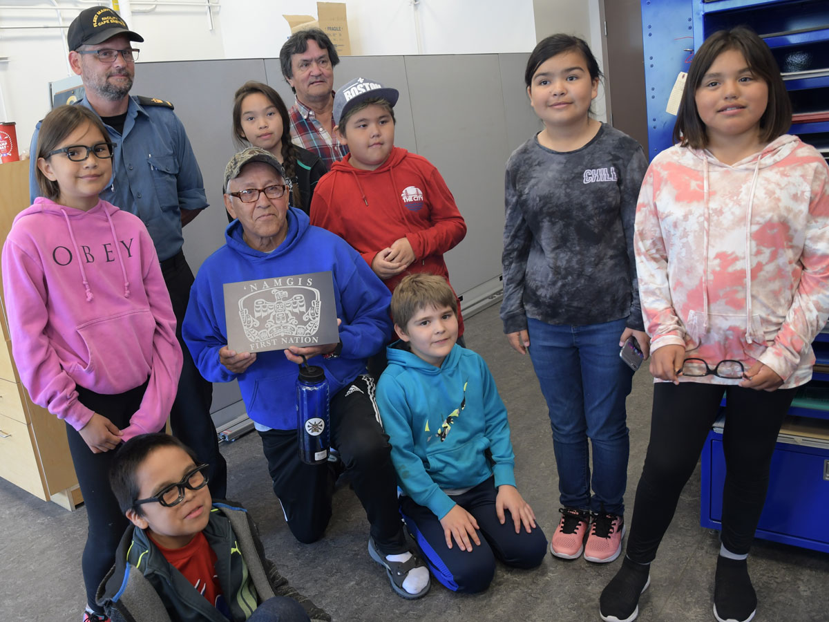 PO1 Wiggins presents Bruce Alfred an engraving of the Namgis First Nation's logo; George Alfred and the students of T'lisalagi'lakw school pose with him in the Fleet Maintenance Facility engraving shop. Photo by SLt M.X. Déry, MARPAC PA Office