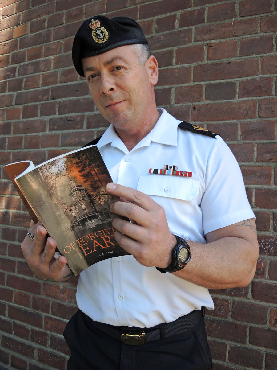 PO1 Steve Pring poses with a copy of his self-published novel Of Forgiving Hearts. Photo by Peter Mallett, Lookout