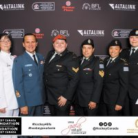 (Left) Valerie Savard, Personnel Support Programs (PSP) Senior Manager Sports, and CPO1 Line Laurendeau of Canadian Fleet Operations pose for a group photograph with Canadian Armed Forces personnel who attended the Hockey Canada Foundation's Gala Dinner in Edmonton on June 18.
