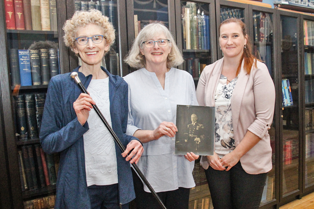 From left, Catherine Blake and Barbara Sybbald, the granddaughters of the late Surgeon Cmdre Archie McCallum, and Arrabelle MacKenzie McCallum, with Naval Museum of Halifax Curator Jennifer Gamble. The visitors donated their late grandfather's drill cane to the museum, along with a collection of photos and documents. Photo by Ryan Melanson, Trident Newspaper