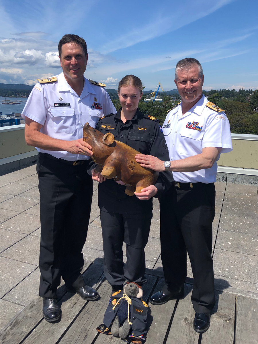 Commodore Angus Topshee (left), Commander Canadian Fleet Pacific; Lieutenant(N) Holly Swallow (centre) of Her Majesty's New Zealand Ship Te Kaha, and Vice-Admiral Art McDonald, Commander Royal Canadian Navy, hold Te Kaha's wooden pig mascot. The mascot was snuck off the ship 20 years ago by the Admiral as a friendly prank.