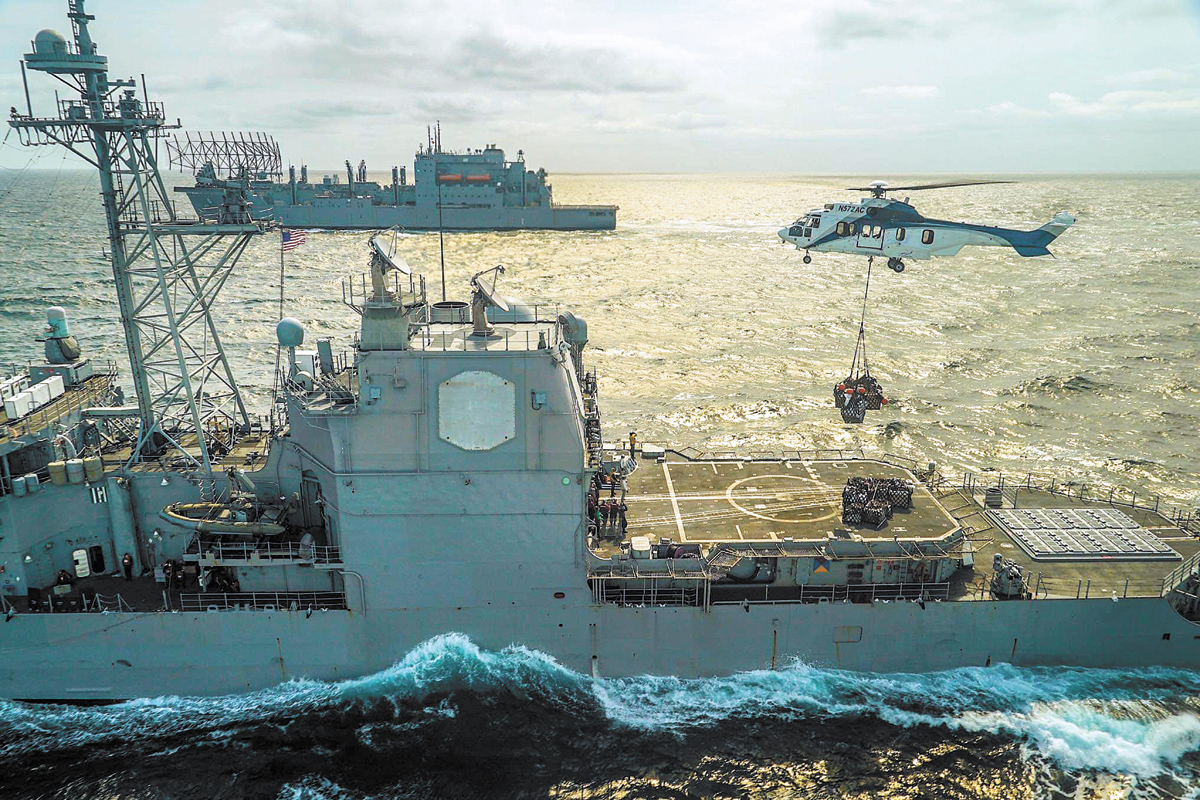 USS Lake Eerie conducts re-supply via helicopter with USNS Amelia Earhart in the background. Photo by Cpl Evans, CFB Borden Base Imaging Services
