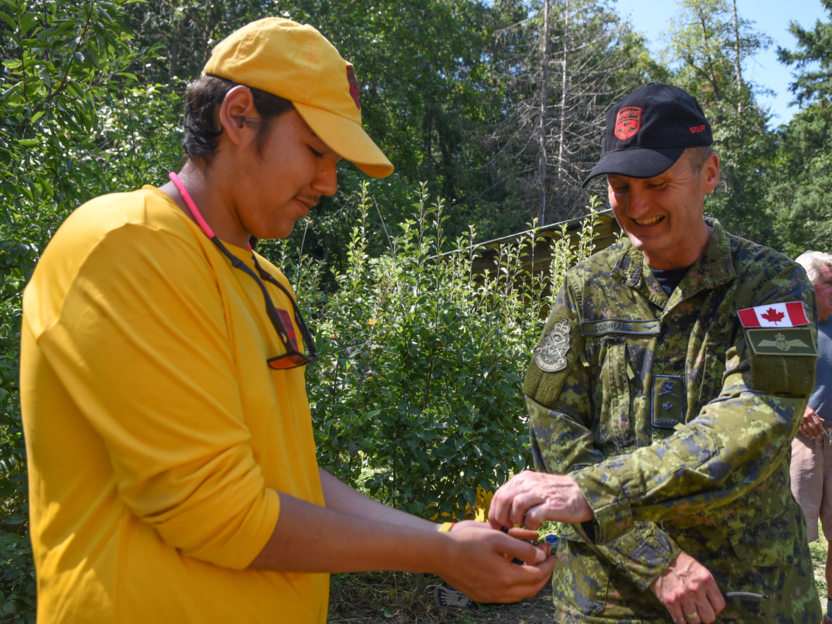 Junior Canadian Ranger Wilbert Shisheesh of Lac Seul, Ont., offers Commander of the National Cadet and Junior Canadian Rangers Support Group, Brigadier-General Dave Cochrane some blackberries during the permaculture workshop held on Aug. 14 at Ruckle Provincial Park on Saltspring Island. Photo by SLt Natasha Tersigni