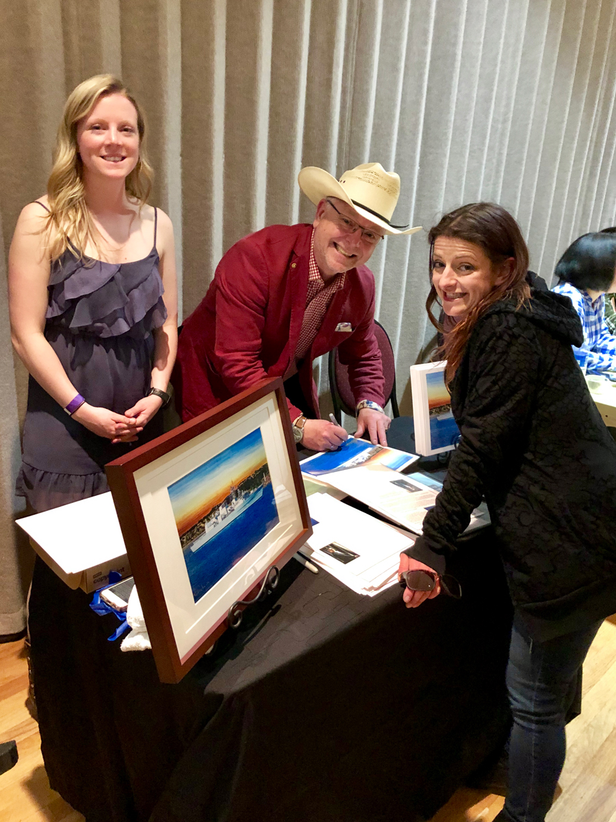 Artist Derek Rickwood signs a print of his HMCS Calgary painting at the ship's Cowboy Up fundraiser on May 11. He is joined by Lt(N) Sonja Maul-Wilson (left) of Canadian Fleet Pacific and Elida Ninami.