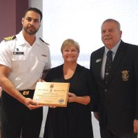 Capt(N) Sam Sader, Base Commander, and Matt Waterman, Navy League of Canada President, present Deborah Walker with a National Presidents' Appreciation Award during a ceremony at the Wardroom, Aug. 23. Photo by Peter Mallett, Lookout