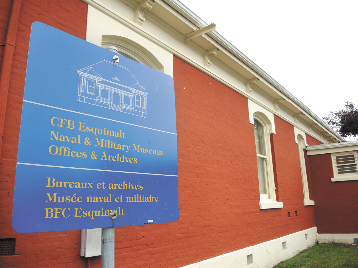 A sign at building N20 marks the offices and archives of the CFB Esquimalt Naval and Military Museum. The building was recently designated as an Historic Place by the Province of British Columbia. Between 1973 and 1984, the red brick building was used as a French-language school and previously served as a residence for admirals and base commanders in the early portion of the 20th century. Photo by Peter Mallett, Lookout