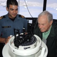 Lt(N) Justin Sowley explains the integration of the pelorus, a reference tool for maintaining bearing of a vessel at sea, with the Naval Bridge Simulator to Cdr (Retired) Doug Henderson. Photo by Peter Mallett, Lookout