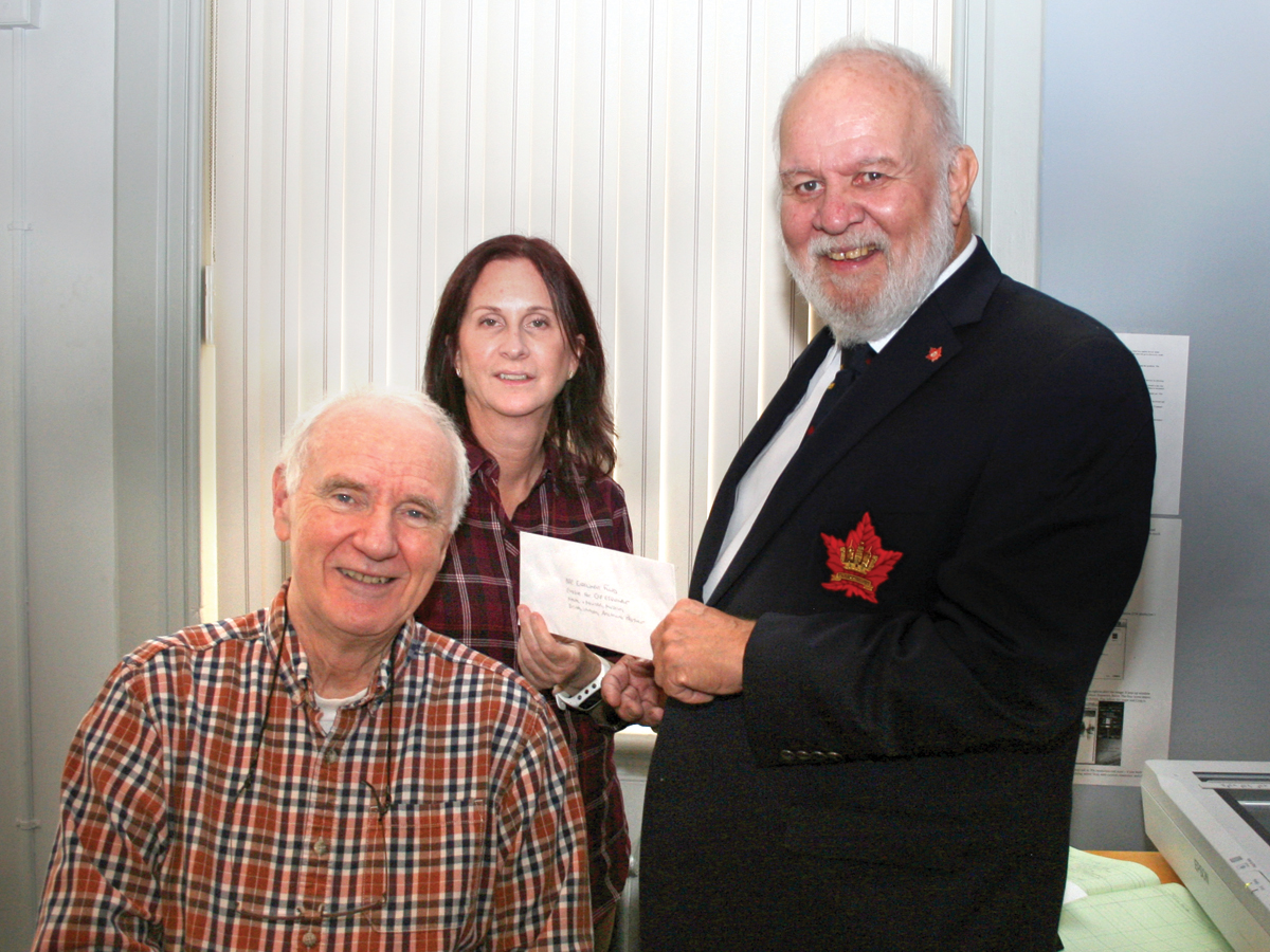 The CFB Esquimalt Military and Naval Museum offices the Naval Association of Canada (NAC), represented by National NAC President Bill Conconi (R) presents a cheque for $2000 from the NAC Endowment Fund to curator Debbie Towell (C) in support of the museum's digital imagery project. Also in attendance was Paul O'Reilly (L), a museum volunteer, who supports the project. Photo by Paul Seguna, NAC-VI