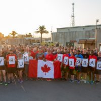 A group of Canadian Armed Forces personnel hold up a Canadian flag after participating in an Army Run at Union III military installation in Baghdad. Photo credit DND