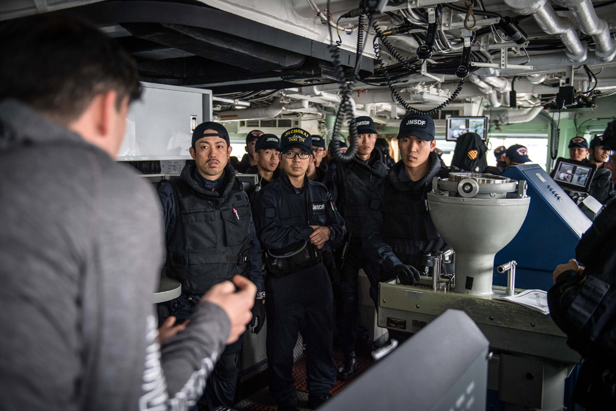 Sub-Lieutenant Riley Perrior discusses  Ottawa's Boarding Party techniques with members of the Japan Maritime Defense Force during a joint naval boarding party exercise onboard HMCS Ottawa on October 16 alongside Yokosuka, Japan while deployed on Operations Projection and Neon. Photos by Leading Seaman Victoria Ioganov