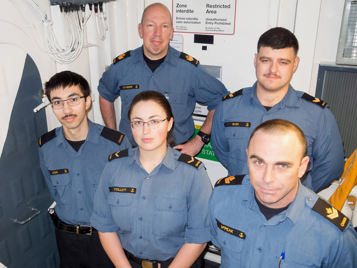 HMCS Ottawa's starboard watch sonar operators gather for a group photo outside their restricted workspace. Back row: PO2 St. Pierre and LS Buss. Front row: OS Legg, AB Collett, and MS McPeak. Photo by Captain Jenn Jackson, HMCS Ottawa PAO