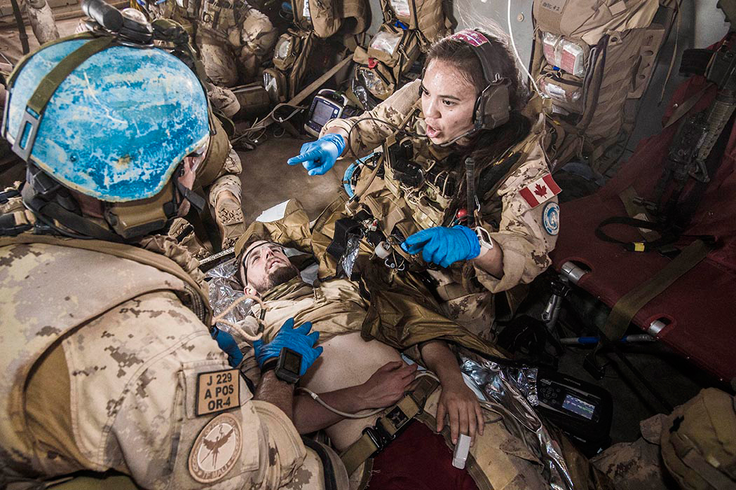 A female member of Task Force-Mali's Canadian Medical Emergency Response Team provides direction during a forward aeromedical evacuation exercise aboard a CH-147F Chinook helicopter in March. Photo by Corporal François Charest, 430 Tactical Helicopter Squadron (430 Tac Hel Sqn)