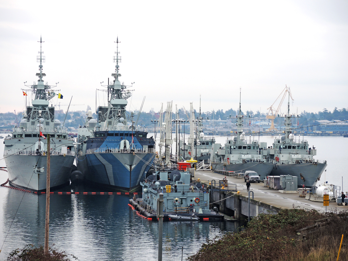 A view of Colwood's crowded 'F' Jetty on Dec. 6. The western end of Esquimalt Harbour was home to five commissioned ships of the Royal Canadian Navy with Halifax-class frigates HMCS Winnipeg and HMCS Regina to the left, and to the right of the Jetty Maritime Coastal Defence Vessels HMC Ships Brandon, Edmonton, and Yellowknife. A fuel barge from the Auxilliary Fleet is in the foreground. Photo by Peter Mallett, Lookout