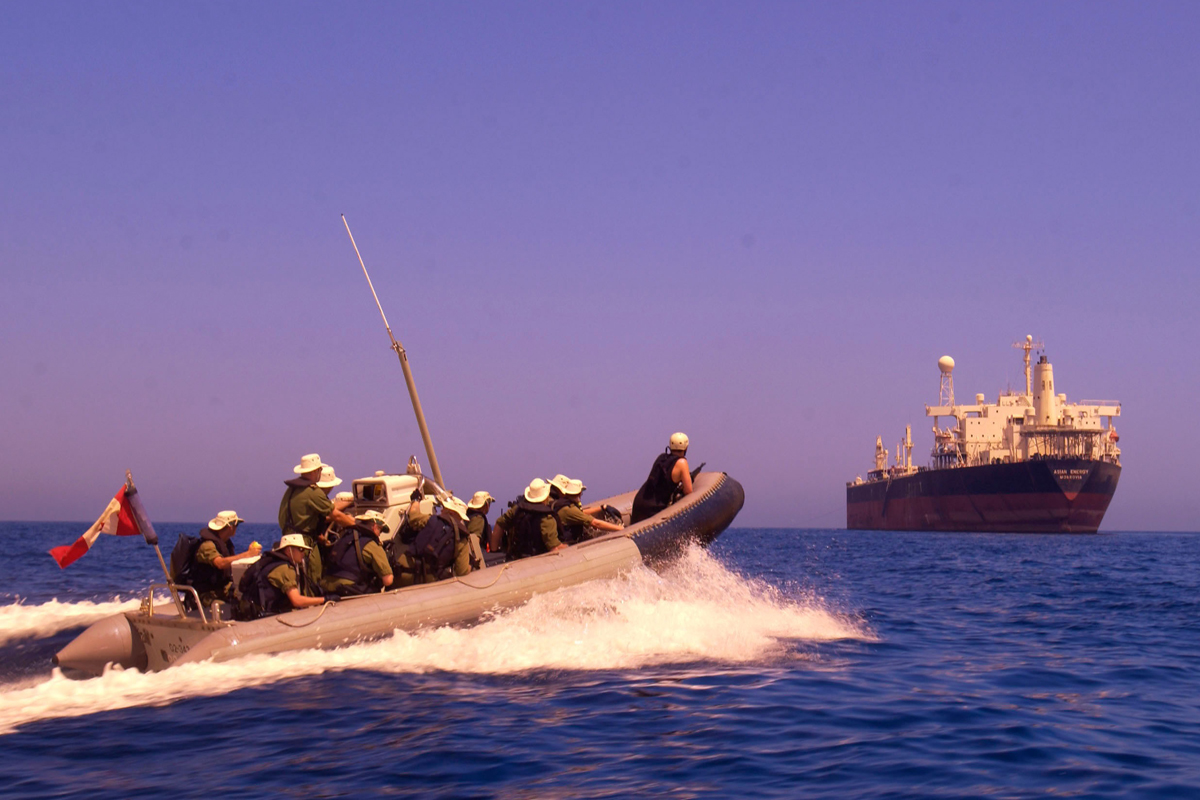 Members of HMCS Regina's naval boarding party make their way in a Rigid Hull Inflatable Boat (RHIB), to a suspect vessel in the Gulf of Oman. Photo by MCpl Frank Hudec, Canadian Forces Combat Camera