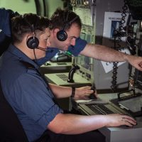 MS Firat Ataman, Forward Fire Control Supervisor, mentors OS Walker Grant as he becomes familiar with the Forward Fire Control Radar Console onboard HMCS Ottawa during Operation Projection.
