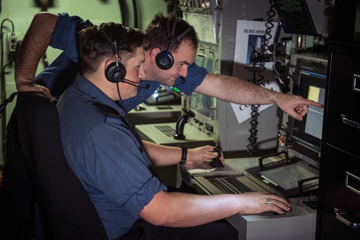 MS Firat Ataman, Forward Fire Control Supervisor, mentors OS Walker Grant as he becomes familiar with the Forward Fire Control Radar Console onboard HMCS Ottawa during Operation Projection. Photo by LS Victoria Ioganov