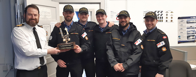 The winning team of this month's Seamanship Olympics, the Temporary Holding Platoon. They are pictured here with the Seamanship Olympics Trophy presented by LCdr Chris Maier.