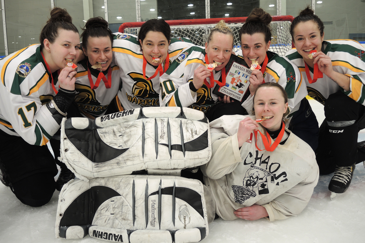 Players from CFB Edmonton Warriors celebrate the taste of victory and bite down on their gold medals after their 4-2 win over CFB Esquimalt Tritons in the championship game of the CAF Canada West Women's Regional Hockey Championship at Wurtele Arena on Feb. 7. Photo by Peter Mallett, Lookout.