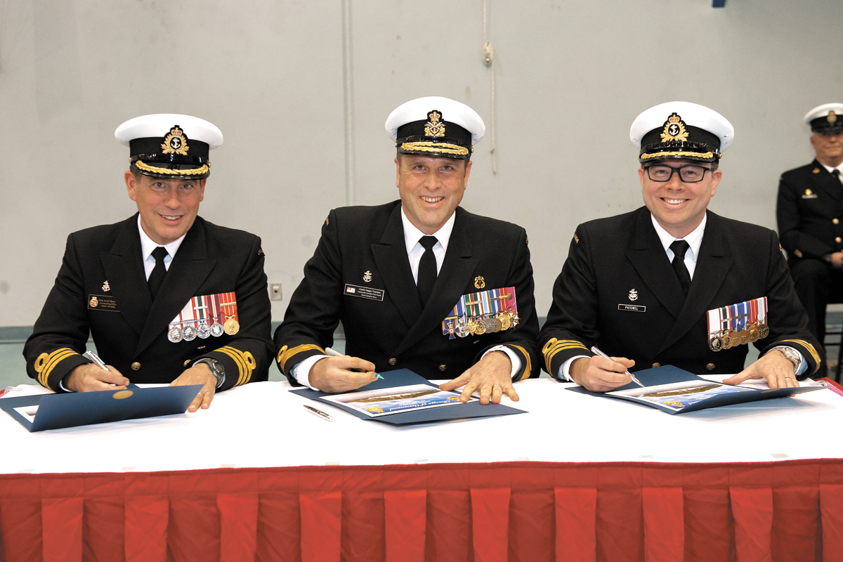 Outgoing Commanding Officer of HMCS Ottawa, Commander Alex Barlow is joined by Commodore Angus Topshee, Commander Canadian Fleet Pacific, and incoming Commanding Officer of HMCS Ottawa, Cdr Sam Patchell during the command handover ceremony Jan. 24.