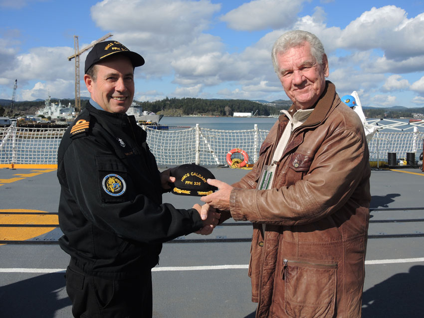 HMCS Calgary Commanding Officer, Cdr Alex Barlow welcomes David McLean aboard for a tour of the warship. Cdr Barlow presented an official captain's hat and coin to McLean to be given to his 100-year-old father Leslie McLean. McLean sailed aboard the original HMCS Calgary vessel during the Second World War. Photo by Peter Mallett, Lookout