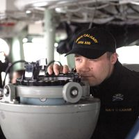 SLt Jason Wychopen takes a bearing from the bridge of HMCS Calgary during Directed Ship Readiness Training.