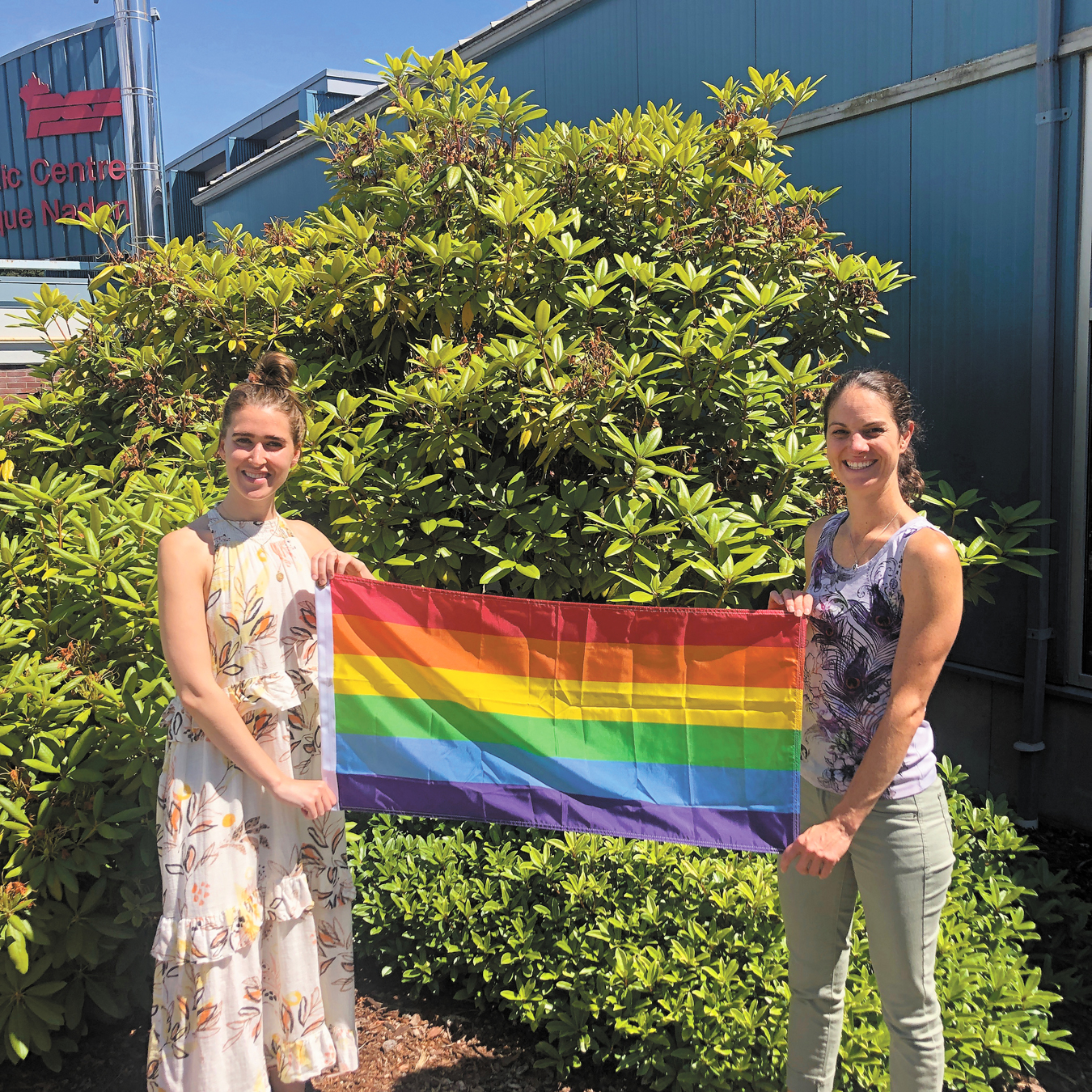 Amy Gordichuk and Alli Jones, members on the Positive Space Working Group, hold up the new Pride flag that is now on a flag pole at CFB Esquimalt.