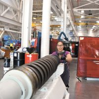 Antoniette Yap, a millwright apprentice at Fleet Maintenance Facility Cape Breton, cleans the 57mm barrel of HMCS Winnipeg's main gun while conducting an inspection of naval ordnance.