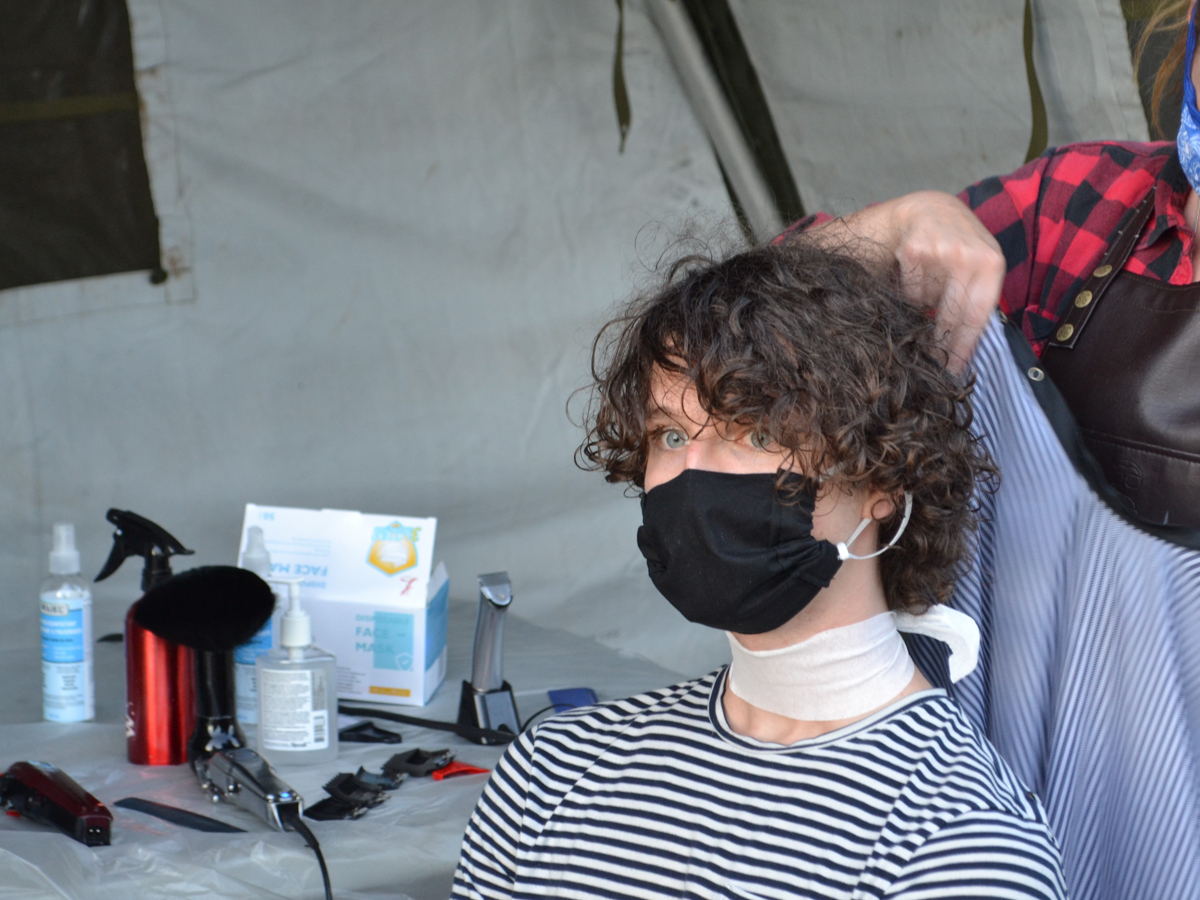 In a makeshift tented barber shop in Work Point, 40 recruits enrolled in Basic Military Qualification training shed their civilian locks for the more formal military look.