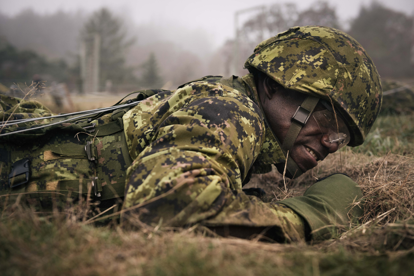 Sailor Third Class Recruit Kofi Asumadu completes the low wire combat crawl obstacle during the Confidence Course as part of BMQ training on Oct. 5. Photo by S1 Victoria Ioganov, MARPAC Imaging Services