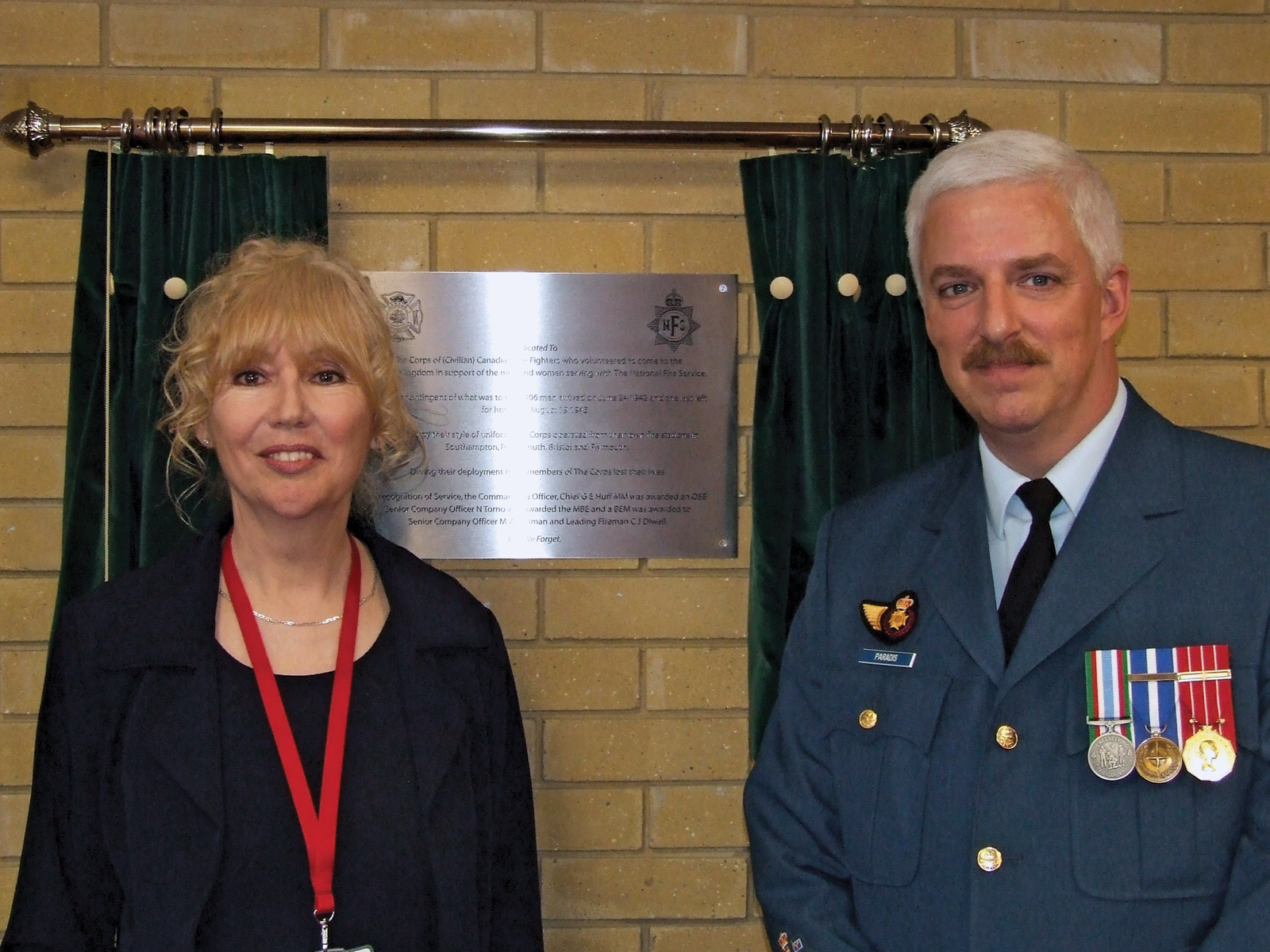 Elaine Bryce, daughter of Gordon Bryce, a member of the Corps of Canadian Firefighters, with CWO Bruce Paradis at the plaque unveiling to honour the Corps.