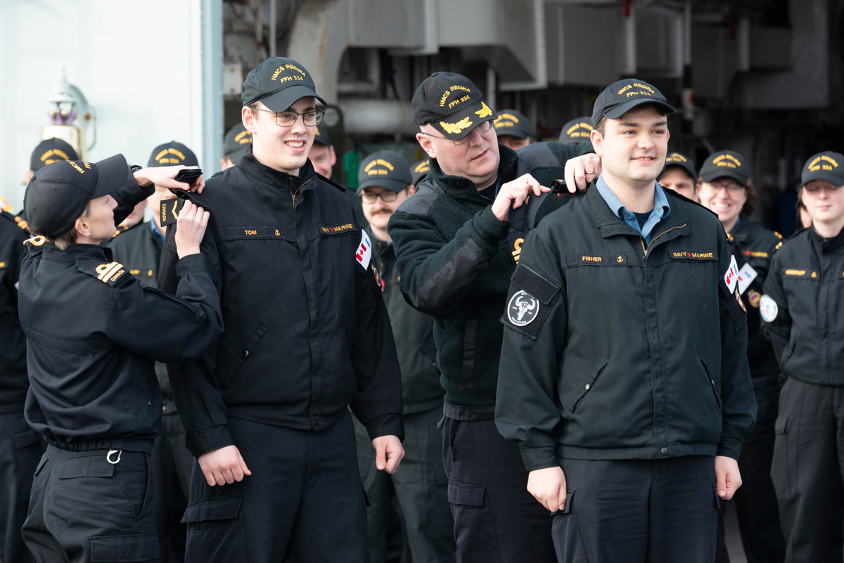 Sailor's Second Class Colton Tom (centre) and Liam Fisher (front) are promoted to their current rank by Commander Landon Creasy (left) and Lieutenant (Navy) Rebbeca Macdonald on board HMCS Regina Feb. 8. Photo by Lieutenant Jeff Klassen, Canadian Armed Forces Photo