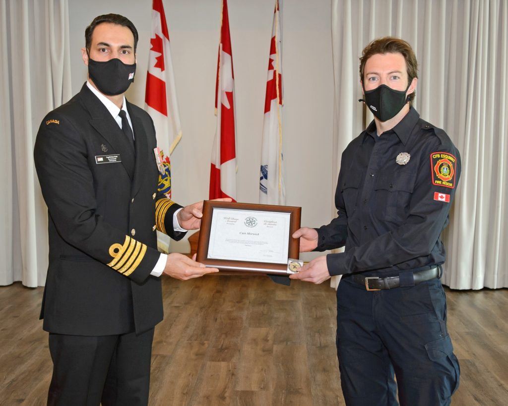 Capt(N) Sam Sader, Base Commander, presents base firefighter Curt Morwick with a Bravo Zulu  for his work to improve the occupational health and safety of his co-workers. Photo by: Sailor First Class (S1) Sisi Xu, MARPAC Imaging Services, Esquimalt