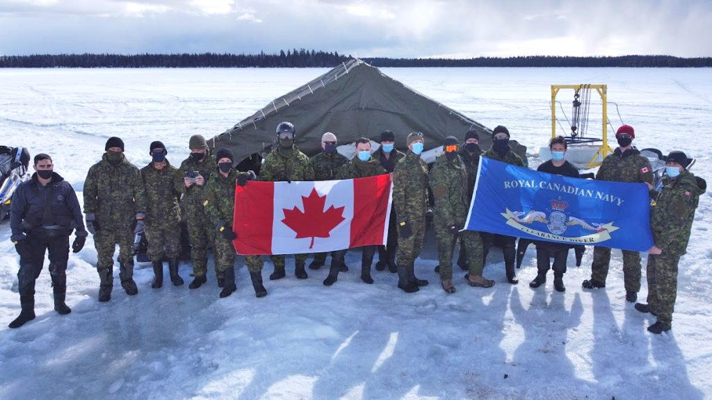 Members of the ICEDIVEX 21 team pose for a group photograph at their dive site out on the lake. Photo by FDU(P)