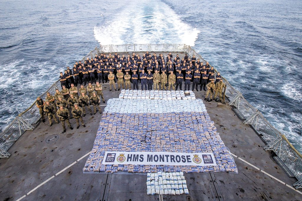 Royal Navy and Royal Marines from HMS Montrose stand with more than 2,800 kilograms of narcotics seized from a vessel in the Arabian Sea on March 12. Photo: AET Josh Edwards RN