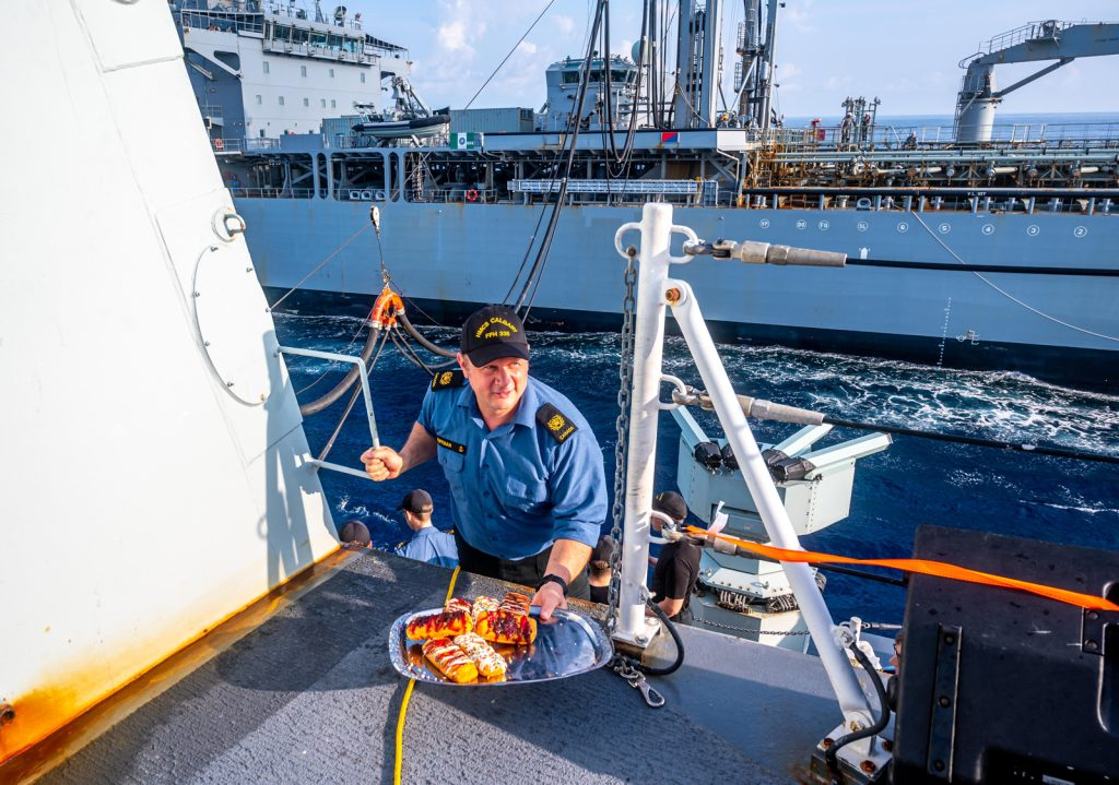 Chief Petty Officer Second Class Paul Huffman serves doughnuts – more specifically RAS doughnuts - to the officers and crew of HMCS Calgary during a replenishment-at-sea (RAS) with Her Majesty's Australian Ship Sirius. Photo by Captain Jeff Klassen, HMCS Calgary