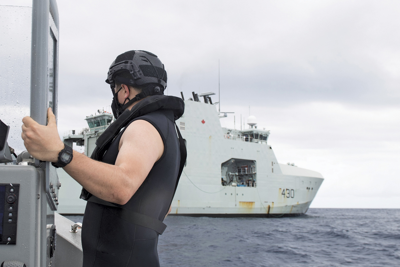 Lt(N) Steven Gallant performs functional tasks on board a rigid-hulled inflatable boat with Harry DeWolf in the background during warm water trials. Photo by Corporal Simon Arcand, Canadian Armed Forces Photo