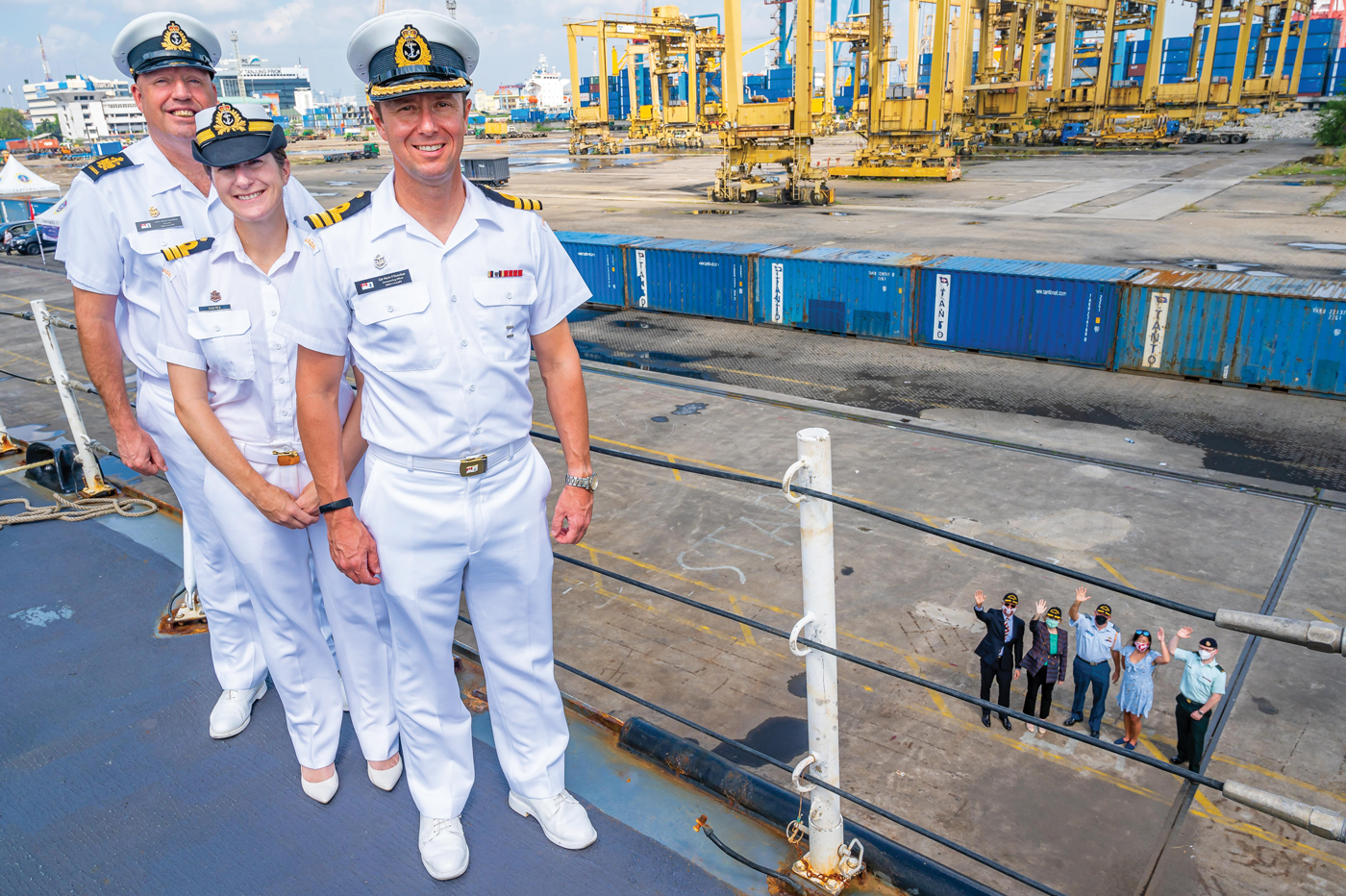 Commander Mark O'Donohue, HMCS Calgary Commanding Officer; Cdr Meghan Coates, Executive Officer; and Chief Petty Officer First Class Mark Chambers, Coxswain, stand on the ship's forecastle as Cameron MacKay, Canadian Ambassador to Indonesia and Timor-Leste; Diedrah Kelly, Canadian Ambassador to the Association of Southeast Asian Nations; Colonel Andrew Cleveland, Canadian Defence Attaché to Indonesia, the Philippines, Brunei and Timor-Leste; and two of their staff members wave farewell from the jetty as the ship was alongside in Jakarta, Indonesia, July 2.